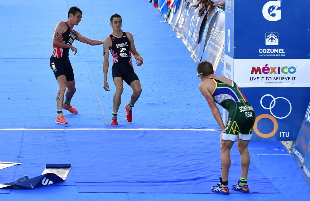 COZUMEL, MEXICO - SEPTEMBER 18: Alistar Brownlee of Great Britain helps his brother Jonathan Brownlee (c) of Great Britain to cross the finished line as Jonathan collapsed of dehydration 200 meters before the finish line during the Men Elite ITU World Championship race at the Fonatur Triathlon Park on September 18, 2016 in Cozumel, Mexico. The medal ceremony was cancelled due to the critical condition of Jonathan Brownlee. The ITU Grand Final World Championship ends tonight. (Photo by Alexander Koerner/Getty Images)